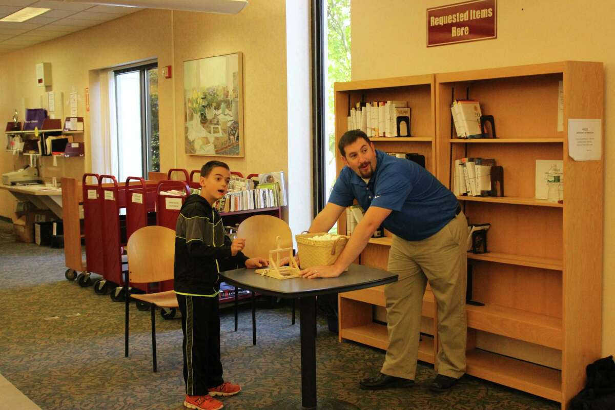 Alec Astorino, 9, launches a marshmallow with Danbury Savings Bank employee Jason Arrowitz at the Mad Hackers STEAM fair held at the Danbury Library on Saturday, Oct. 17, 2015.