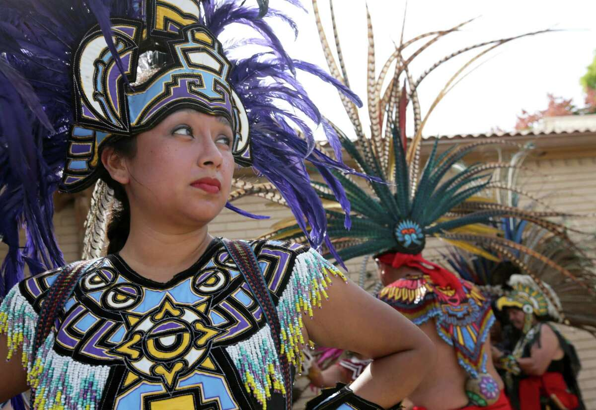 Marisela Orozco, a member of Danza Azteca Taxcayolutl, watches the crowd before performing at the East End Street Fest on Navigation Boulevard, Saturday, Oct. 17, 2015, in Houston.