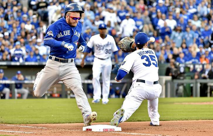 Toronto Blue Jays' Josh Donaldson, left, reaches first base as he legs out an infield hit as Kansas City Royals first baseman Eric Hosmer (35) fields the late throw during the sixth inning in Game 2 of baseball's American League Championship Series, Saturday, Oct. 17, 2015, in Kansas City, Mo. (Nathan Denette/The Canadian Press via AP) MANDATORY CREDIT