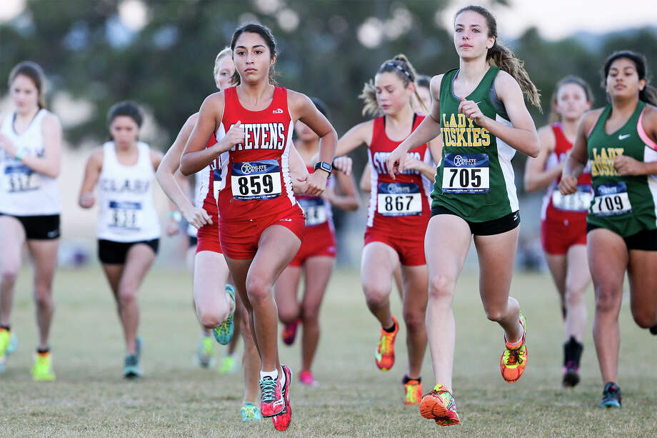 Stevens' Elizabeth Alvarado (859) runs to the lead with Holmes' Madison Howard (705) at the start of the varisty girls 5K during the District 27-6A cross country championships at Brandeis High School on Saturday, Oct. 17, 2015.  Alvarado won the event with a time of 19:17.287.  Howard finished fifth.  MARVIN PFEIFFER/ mpfeiffer@express-news.net Photo: Marvin Pfeiffer, Staff / San Antonio Express-News / Express-News 2015