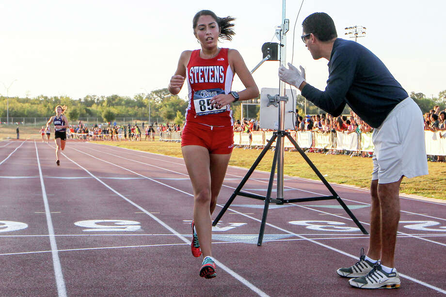 Stevens' Elizabeth Alvarado crosses the finish line ahead of Warren's Hunter Paul in the varisty girls 5K during the District 27-6A cross country championships at Brandeis High School on Saturday, Oct. 17, 2015.  Alvarado won the event with a time of 19:17.287. Paul finished second with 19:05.206.  MARVIN PFEIFFER/ mpfeiffer@express-news.net Photo: Marvin Pfeiffer, Staff / San Antonio Express-News / Express-News 2015