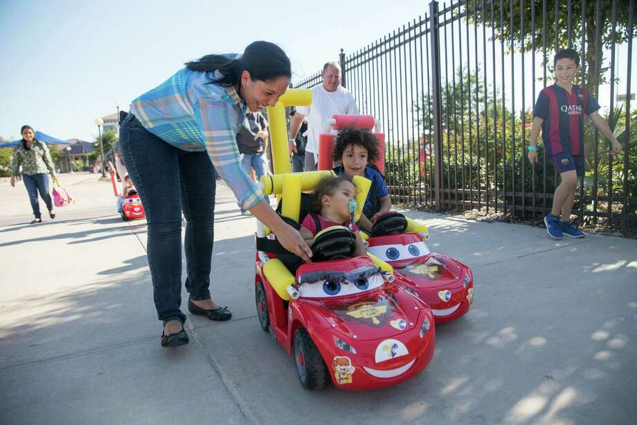 Nelly Hermosa helps her 22-month-old daughter, Leticia Vivas, steer her motorized toy car in a race during the first Go Baby Go seminar and interactive build workshop for pediatric rehabilitation patients and their families at Morgan's Wonderland. Photo: Photos By Carolyn Van Houten /San Antonio Express-News / 2015 San Antonio Express-News