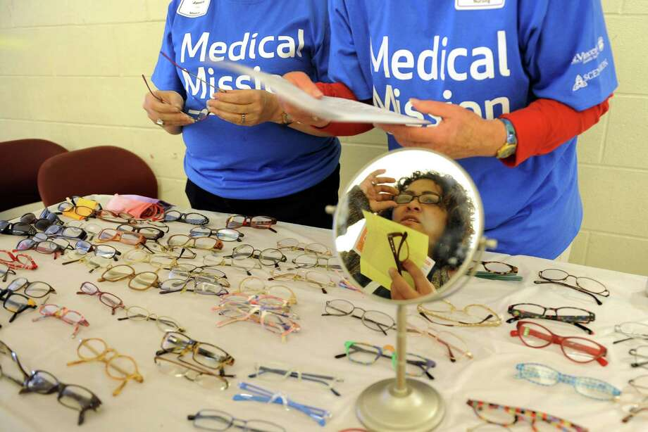"Leslie Fernandez, of New Haven, tries out a pair of glasses which were given out as part of St. Vincent's first ""Medical Mission at Home"" held at Cesar Batalla School in Bridgeport, Conn. on Saturday October 17, 2015. Volunteer medical staff and associates offered medical exams and podiatry services, behavioral health services, connections to community providers, follow-up care, and more. All services were offered free to individuals 18 years and older, and no insurance was required. Photo: Christian Abraham, Hearst Connecticut Media / Connecticut Post"