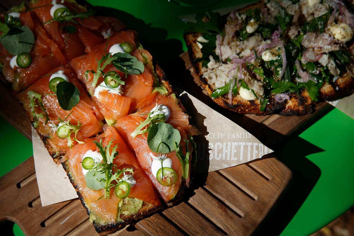 The cured bruschetta plate with smoked salmon, chilies, creme fraiche and avocado, left, and the porchetta bruschetta plate with Bailey and Long Farms pig, garden herbs, red onion, aioli and parmesan at the Clif Family Bruschetteria, a bruschetta truck parked outside the Velo Vino tasting room in St. Helena, Calif., on Sunday, October 11, 2015.