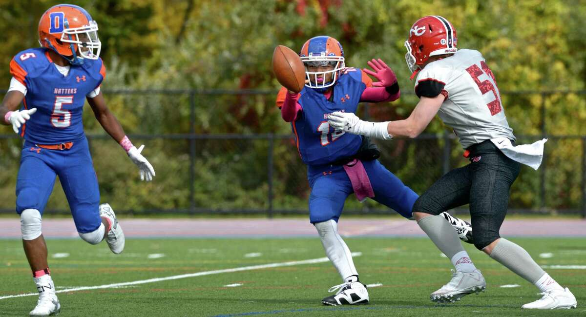 Danbury quarterback Jordan Khuth (18) pitches the ball to team mate Tyren McCrea (5) before being hit by New Canaan's Andrew Chalon (53) in the football game between New Canaan and Danbury high schools on Saturday afternoon, October 17, 2015, played at Danbury High School, Danbury, Conn.
