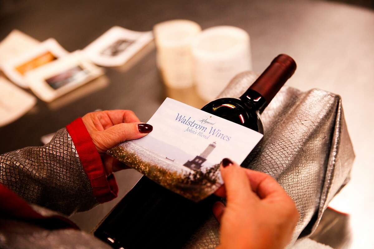 Kathy Walstrom, of Glenview, Ill., puts the label she created on the bottle of wine she made in honor of her late husband during the Winemaker for a Day class at Raymond Vineyard in St. Helena, Calif., on Monday, October 12, 2015.