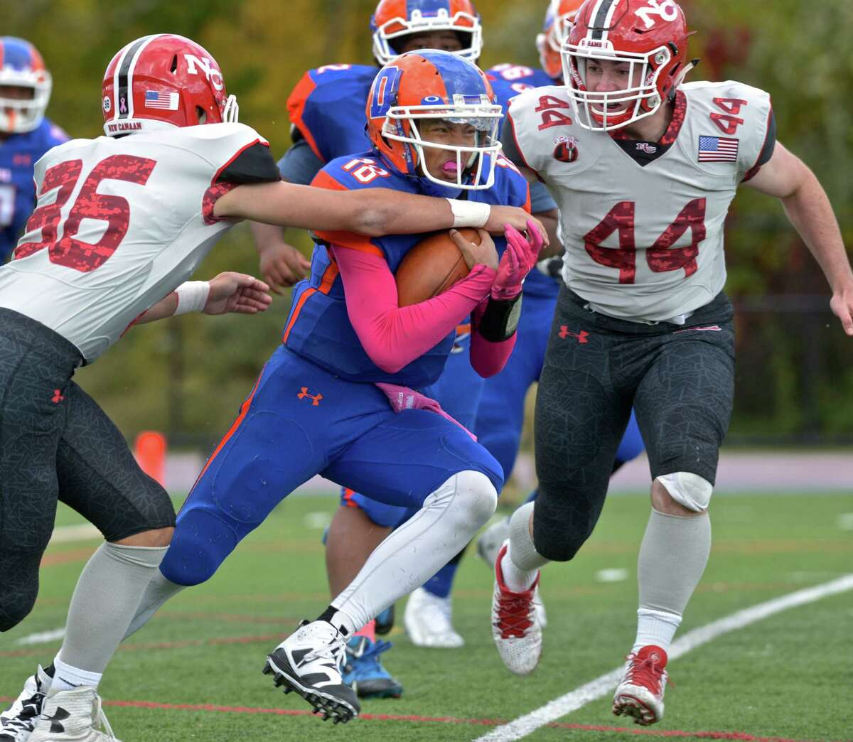 Danbury's Jordan Khuth (18) tries to squeeze between new Canaan's Andrew Bauerfeld (36) and Peter O'Sullivan (44) during their game Saturday Danbury High School.