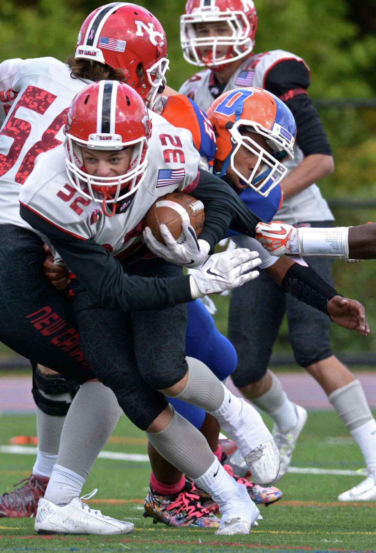 New Canaan's Graham Braden (32) breaks free with a block by team mate Teddy Hood (58) on Danbury's Marshal Vines (15) in the football game between New Canaan and Danbury high schools on Saturday afternoon, October 17, 2015, played at Danbury High School, Danbury, Conn.