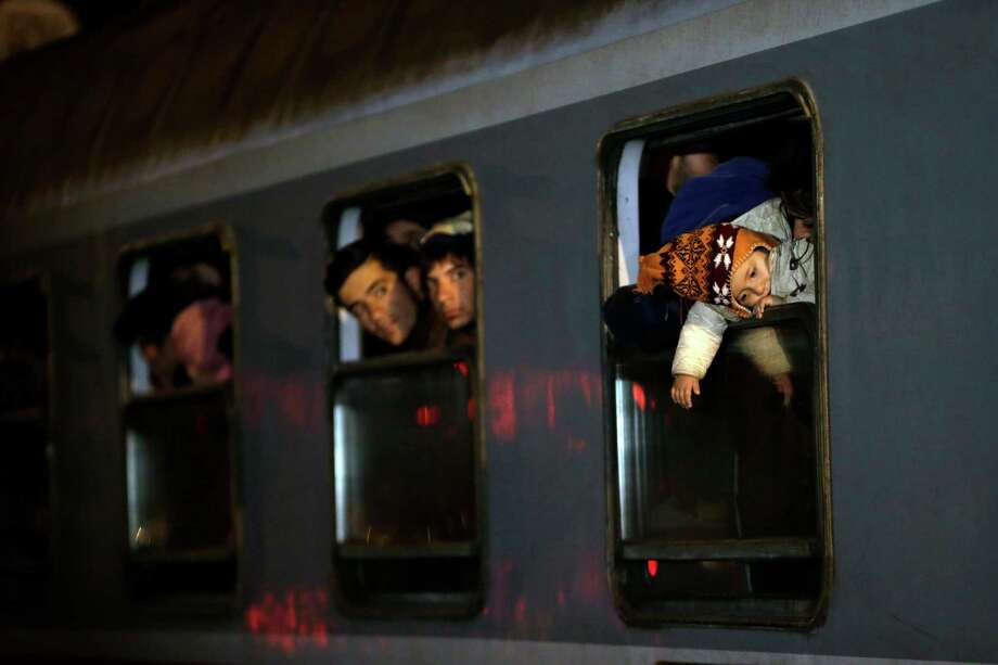 Migrants look out of a train as they arrive from Croatia into Slovenia. After Hungary closed its border with Croatia to the free flow of migrants, Croatia redirected thousands of people toward its border with Slovenia. Photo: Petr David Josek /Associated Press / AP