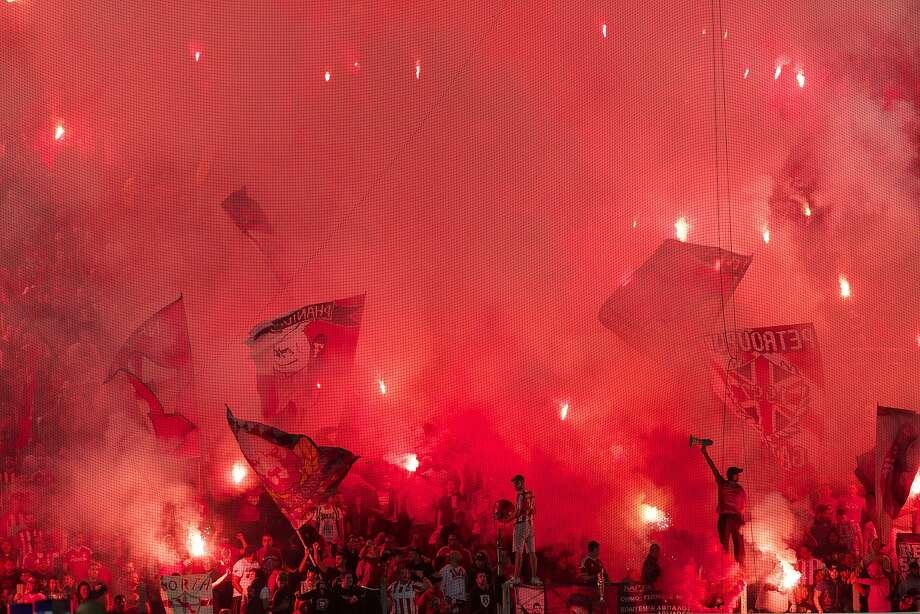 Olympiakos' fans light flares before a Greek Super League soccer match against AEK Athens at the Georgios Karaiskakis stadium in Piraeus port, near Athens, Saturday, Oct. 17, 2015. Photo: Yorgos Karahalis, Associated Press