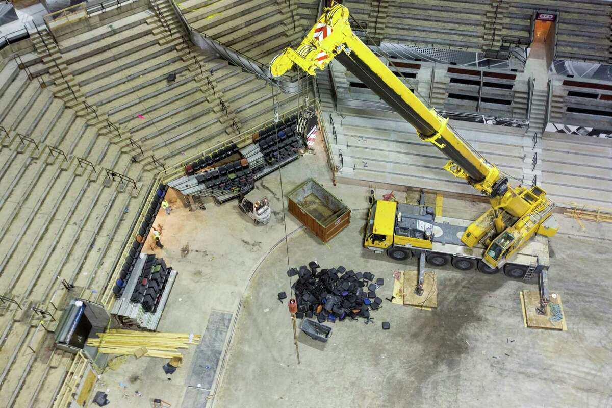 A crane stands Tuesday June 9, 2015 in the middle of the AT&T Center floor as it removes sections of chairs as part of the arena's renovation.