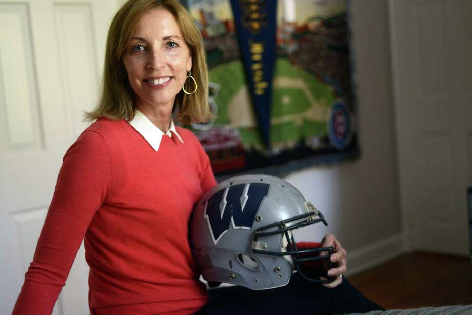 Diana Coyne holds her son's football helmet in his former bedroom at her home in Westport, Conn. Coyne, whose son played football throughout his youth and for one year in college, has actively lobbied for concussion safety. Photo: Autumn Driscoll / Hearst Connecticut Media / Connecticut Post