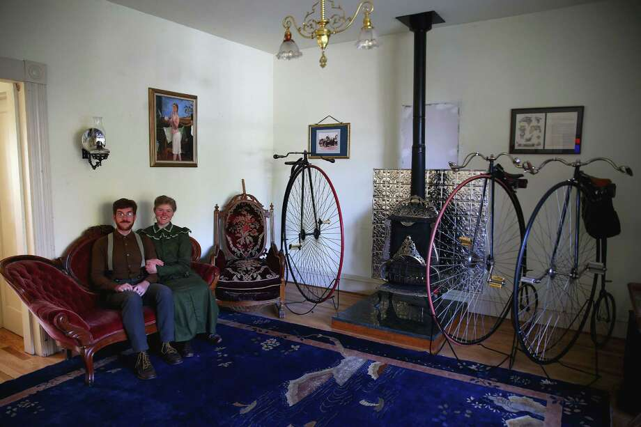Sarah and Gabriel Chrisman began forgoing modern conveniences to live a Victorian-era lifestyle six years ago.  Now the parlor of their home in Port Townsend is lined with period furniture and their collection of 19th Century big wheel bicycles. Photo: GENNA MARTIN, SEATTLEPI.COM / SEATTLEPI.COM