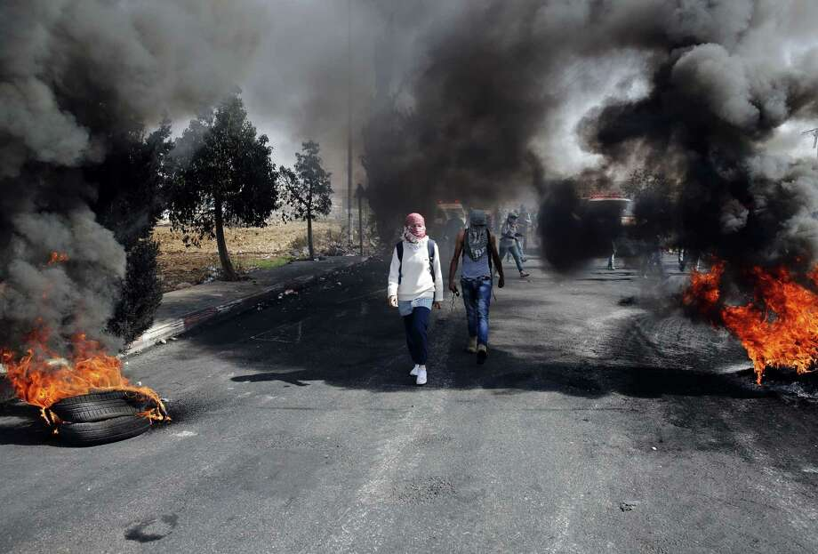 "Palestinian protesters walk between burning tires during clashes with Israeli security forces near the Beit El settlement on the outskirts of Ramallah in the West Bank, on October 17, 2015. The violence that has raged for more than two weeks prompted a ""very concerned"" US President Barack Obama to call for calm as the UN Security Council held an emergency meeting a day earlier. AFP PHOTO / ABBAS MOMANIABBAS MOMANI/AFP/Getty Images Photo: ABBAS MOMANI, Stringer / AFP / Getty Images / AFP"