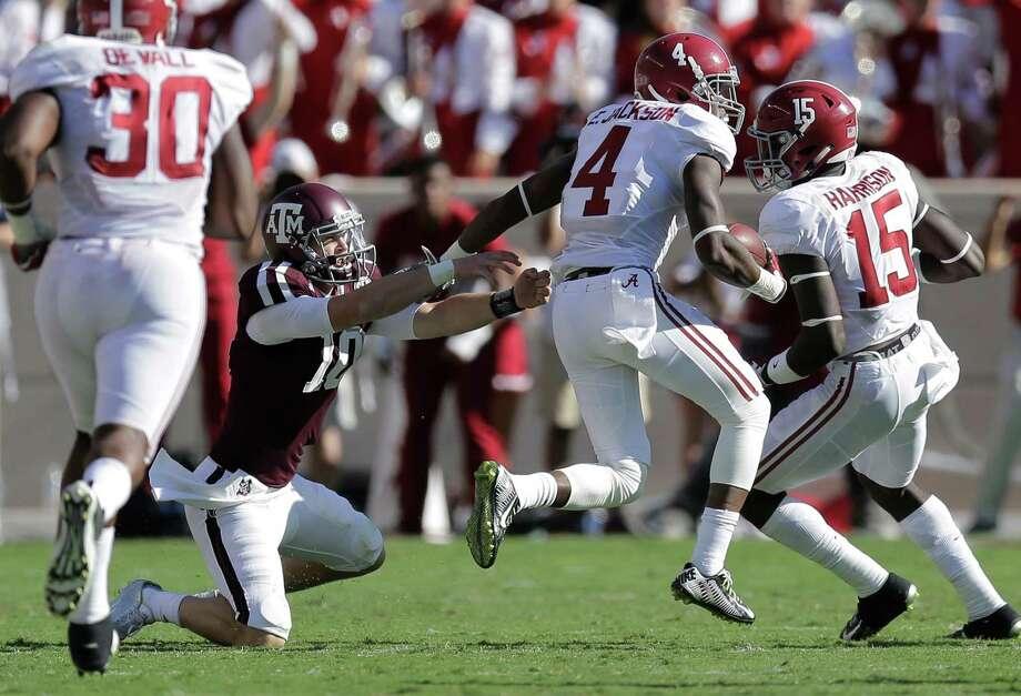 Alabama 's Eddie Jackson (4) runs past Texas A&M quarterback Kyle Allen (10) as he returns an interception for a touchdown during the first half of an NCAA college football game, Saturday, Oct. 17, 2015, in College Station, Texas. (AP Photo/Eric Gay) Photo: Eric Gay, STF / Associated Press / AP