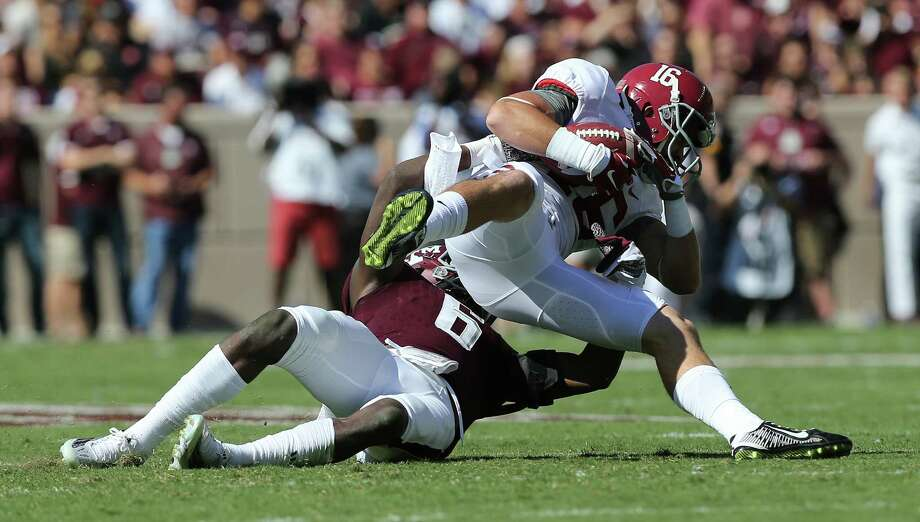 Alabama's Richard Mullaney makes a first-down reception and is pulled down by A&M's Donovan Wilson during the first quarter Saturday at Kyle Field. Photo: Elizabeth Conley, Staff / © 2015 Houston Chronicle