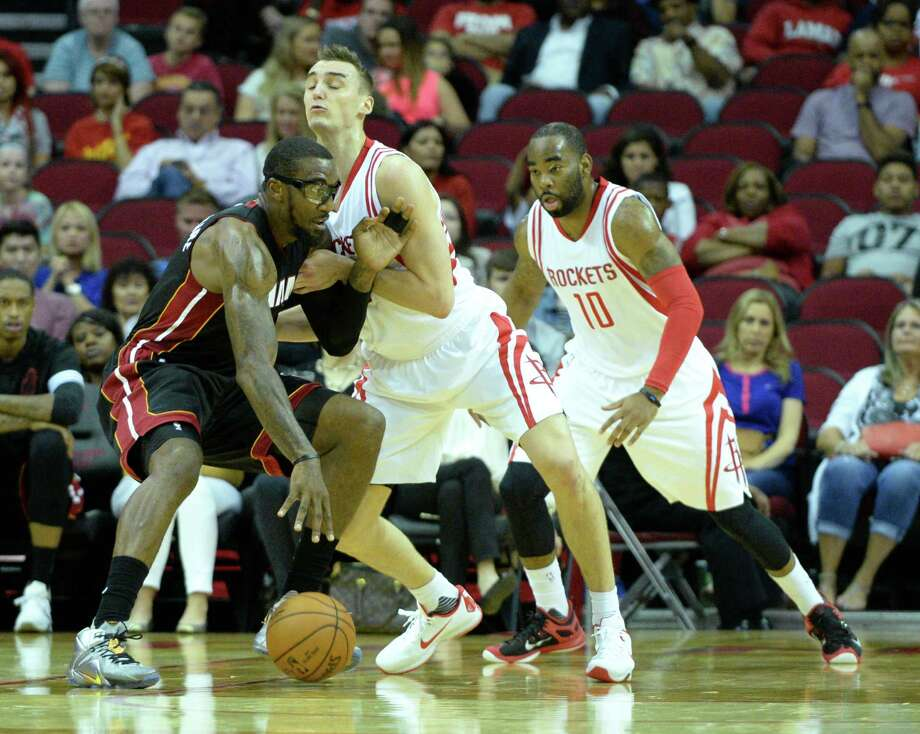 Rockets rookie forward Sam Dekker, center, plays tight defense on Heat forward Amar'e Stoudemire. Dekker had eight points and three rebounds in a little more than 14 minutes off the bench. Photo: Jon Shapley, Staff / © 2015  Houston Chronicle