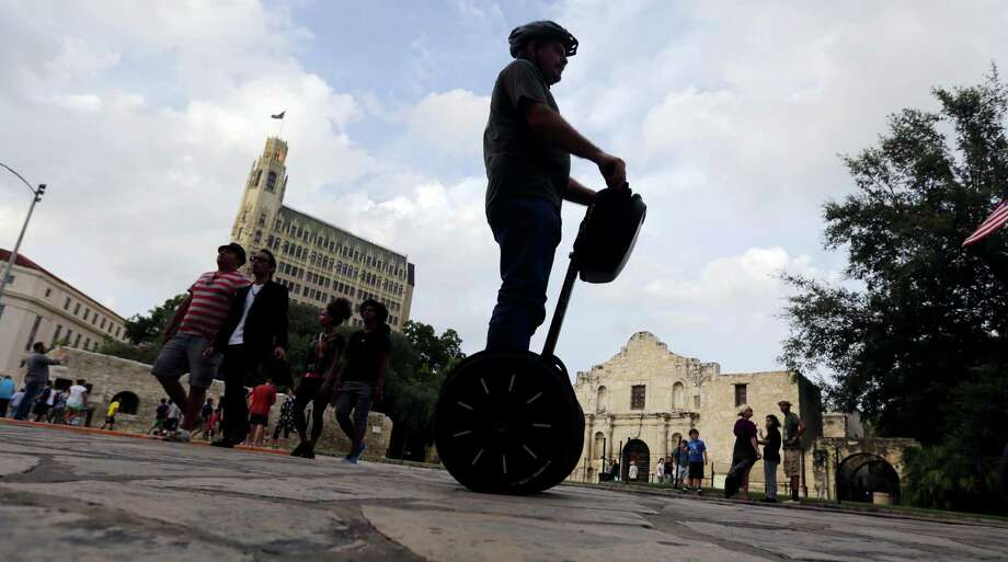FILE - In this July 8, 2015, file photo, a visitor passes the Alamo on a Segway, in downtown San Antonio. The former 18th century Spanish mission is poised to undergo one of the most significant transformations in its history as the state moves to purchase nearby commercial buildings and launch a planning review that could bring dramatic changes. (AP Photo/Eric Gay, File) Photo: Eric Gay, STF / Associated Press / AP