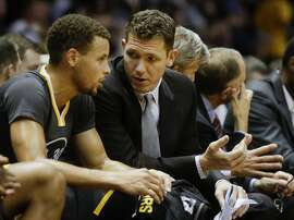 Golden State Warriors interim coach Luke Walton talks with guard Stephen Curry in the first half of an NBA preseason basketball game Saturday, Oct. 17, 2015, in San Diego.  (AP Photo/Lenny Ignelzi)