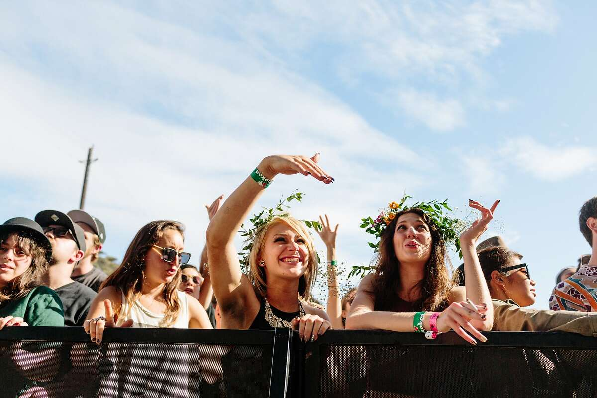 Festival goers in the front row wear flowers in their hair at Treasure Island Music Festival in San Francisco, Calif., Saturday, October 17, 2015.