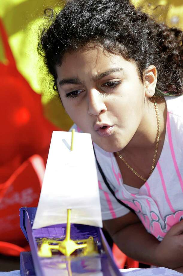 Sohayla Ortiz, 9, works to blow a toy sailboat during exhibit of wind power at the GDF SUEZ Energy booth during the Energy Day Festival at Sam Houston Park, 1000 Bagby St., Saturday, Oct. 17, 2015, in Houston.The free energy education presented by Consumer Energy Alliance targets K-12 students. Photo: Melissa Phillip, Houston Chronicle / © 2015 Houston Chronicle
