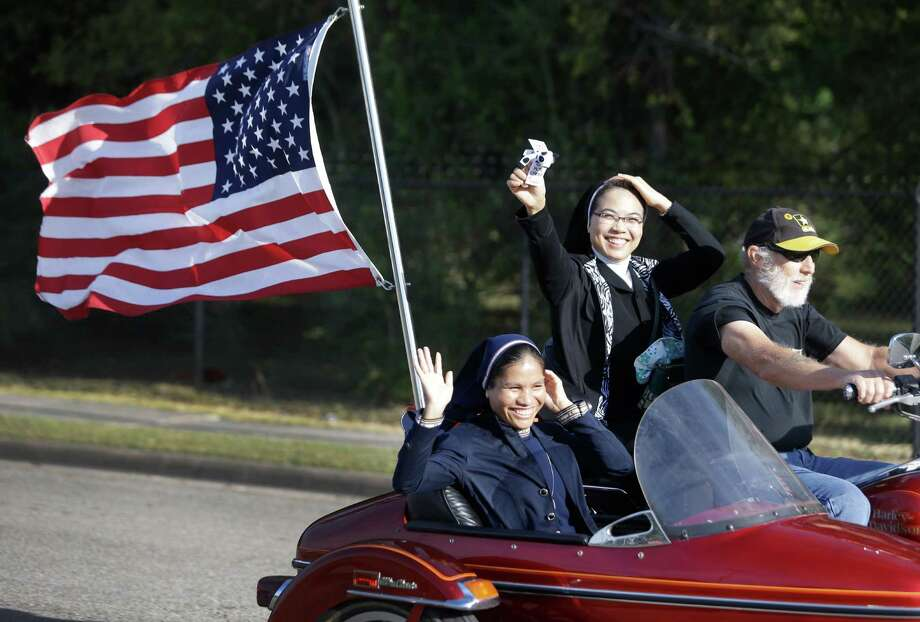 Sister Mary Thao Vu, left, sitting in the side car and Sister Christine Dung, center, wave and hold onto their habits as they are given a ride by Dennis Omo on his Harley Davidson Road King before the start of the 11th Annual Nun Run at St. Austin Center, 2002 S. Wayside Drive, Saturday, Oct. 17, 2015, in Houston. The 40 mile ride to San Leon benefits the CHRISTUS Foundation for HealthCare school-based clinics, which provide healthcare to children on campus in 17 low-income neighborhood schools. Photo: Melissa Phillip, Houston Chronicle / © 2015 Houston Chronicle
