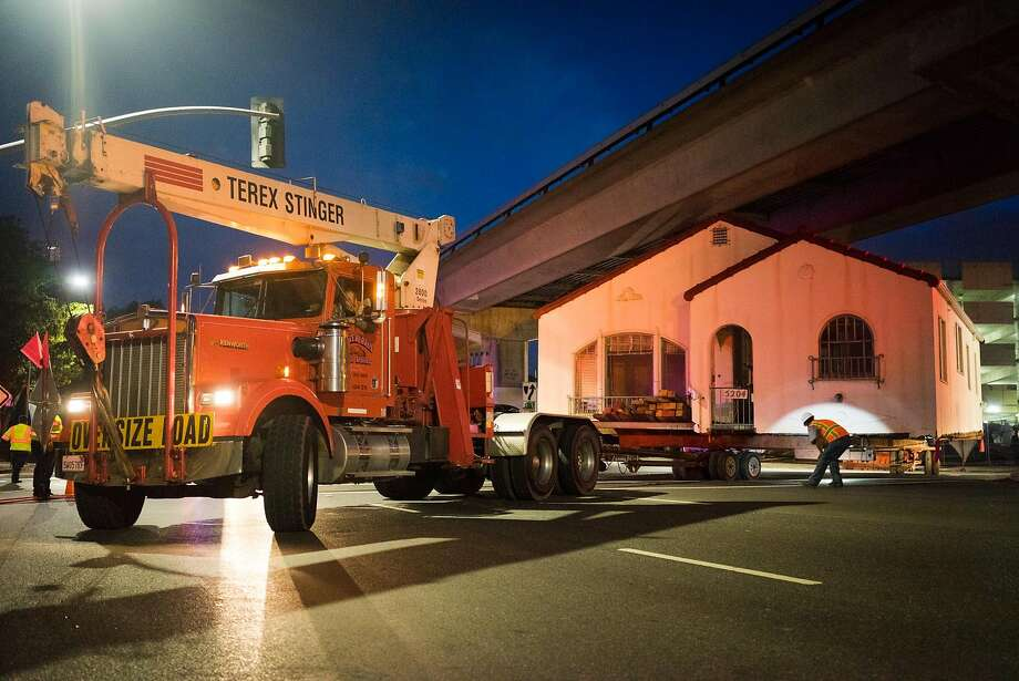 Workers move the house on 5204 Martin Luther King Jr. Way under the BART tracks in Oakland, Calif. on Sunday, Oct. 18, 2015. Despite the house being surrounded by parking garages, the owner refused to sell. Photo: James Tensuan, Special To The Chronicle