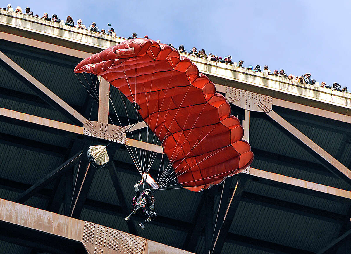 Spectators atop the deck peek over the wall to watch as a BASE jumper glides to Earth during the Bridge Day festival Saturday, Oct. 17, 2015, in Fayetteville, W.Va. Saturday's event is the one day a year that it's legal to jump off the 876-foot high span across the New River Gorge.