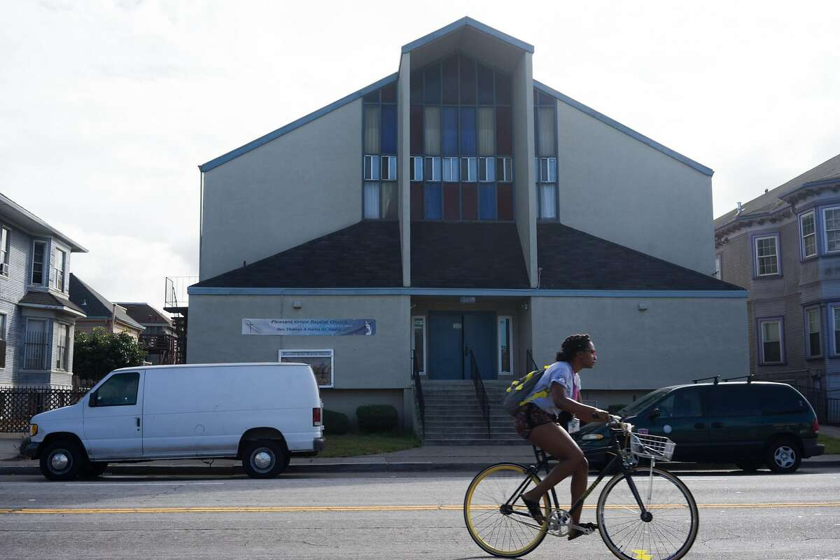 A woman bikes by the Pleasant Grove Baptist Church in Oakland, Calif. on Sunday, Oct. 18, 2015. The city has threatened the church with a $500 dollar a day fine if they continue to violate an order to keep the noise down.