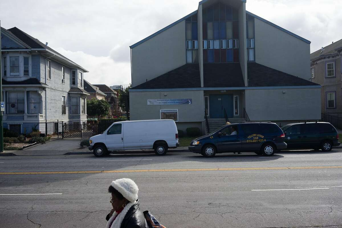 A woman passes by the Pleasant Grove Baptist Church in Oakland, Calif. on Sunday, Oct. 18, 2015. The city has threatened the church with a $500 dollar a day fine if they continue to violate an order to keep the noise down.