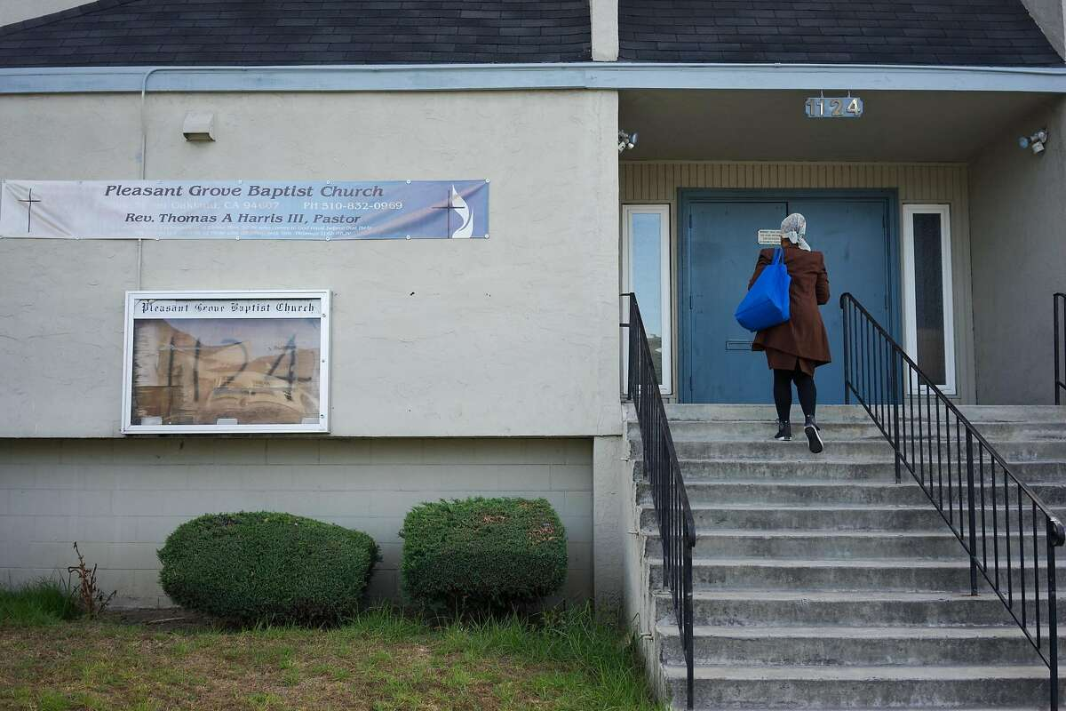 A woman enters the pleasant Grove Baptist Church in Oakland, Calif. on Sunday, Oct. 18, 2015. The city has threatened the church with a $500 dollar a day fine if they continue to violate an order to keep the noise down.