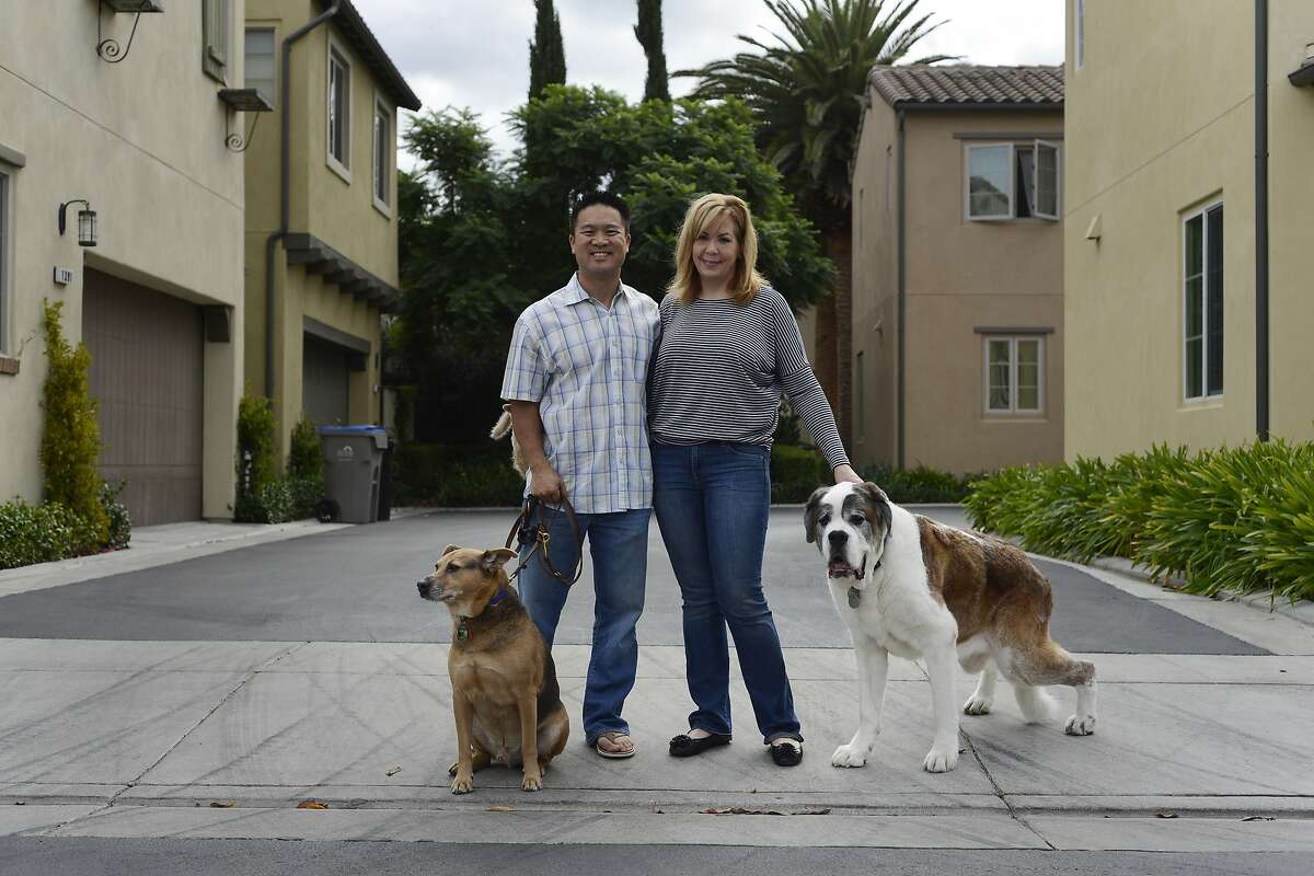 FILE - Michael Leung and his dog Cooper (left) and Suzanne Kisting and her dog Moose (right) pose for a photo in San Jose, Calif., on Saturday, Oct. 18, 2015. Moose takes two 1ml doses of the CBD medicine every day with a mild pain killer to help with the pain of arthritis.