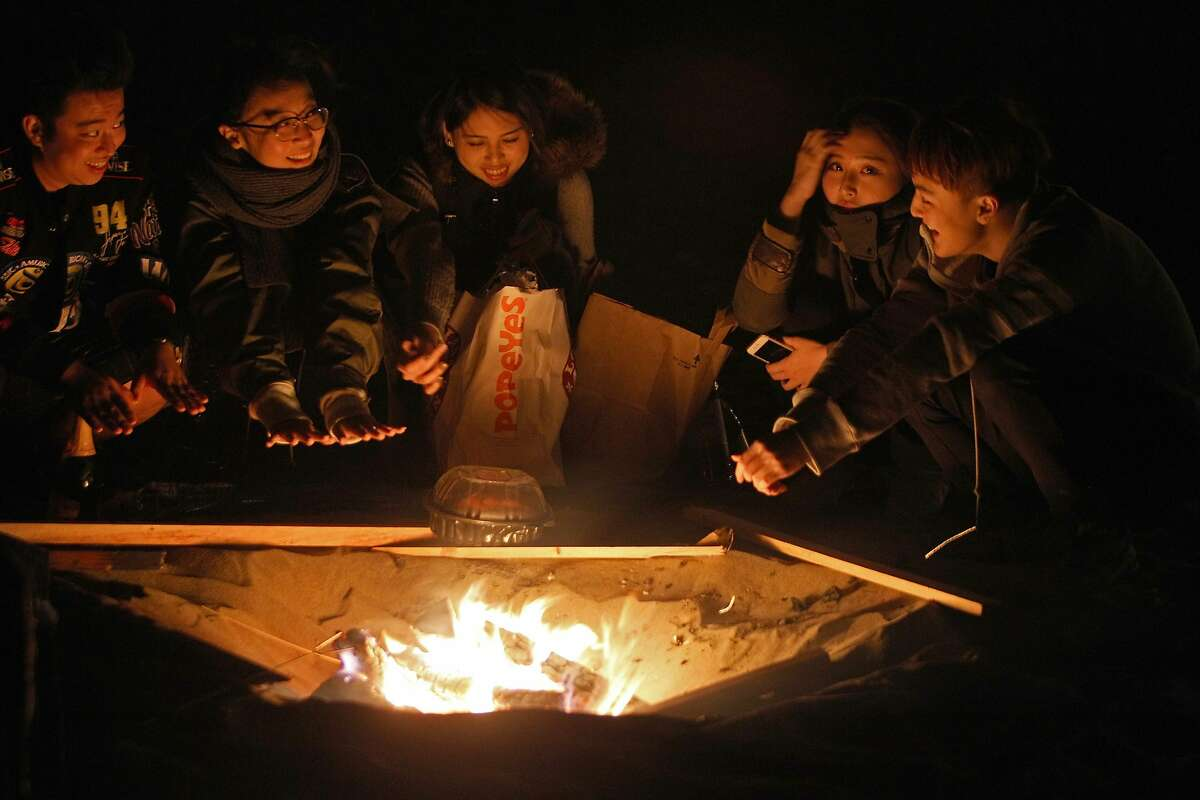 Hanging out at Ocean Beach enjoying their campfire and the mild weather, left to right, Academy of Art students Ren Kaws, 21, Rosemary Xue, 21, Lisa Wang, 20, Stella Yang, 19, and Daniel Chang 19 on October 18, 2015.