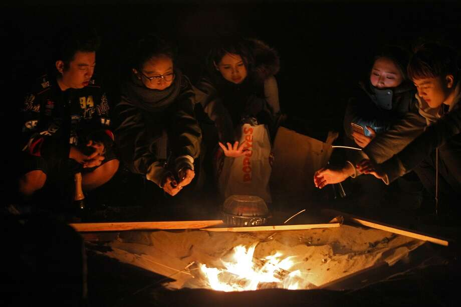 Hanging out at Ocean Beach enjoying their campfire and the mild weather, left to right, Academy of Art students Ren Kaws, 21, Rosemary Xue, 21, Lisa Wang, 20, Stella Yang, 19, and Daniel Chang 19 on October 18, 2015. Photo: Franchon Smith, The Chronicle