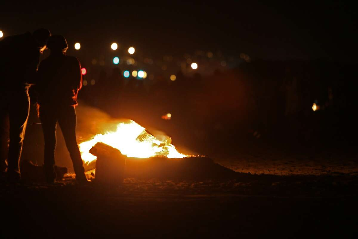 Emaly Torres, 21, of Lafayette and Omar Reynoso, 22, of Vallejo spend their evening at San Francisco's Ocean Beach enjoying a bonfire on October 17, 2015.