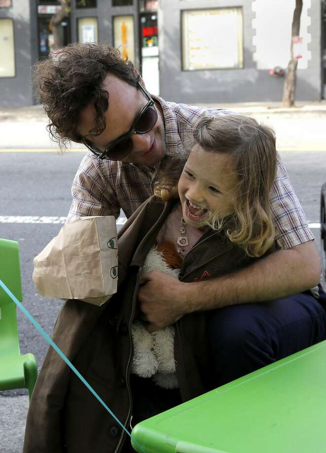 Warren Huegel and Vida Huegel, 4, play with a paper bag puppet at Sunday Streets festival in San Francisco, California, on Sunday, Oct. 18, 2015. Photo: Connor Radnovich, The Chronicle