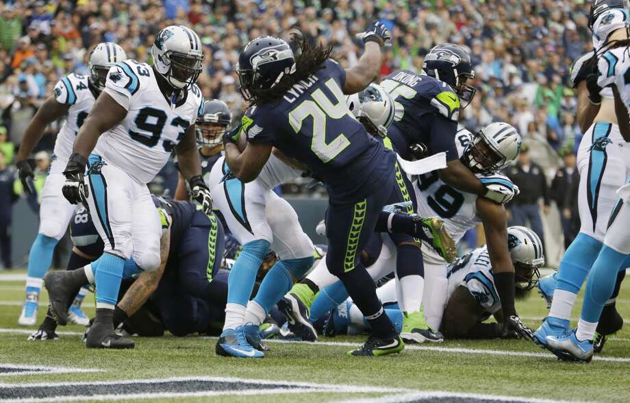Seattle Seahawks running back Marshawn Lynch (24) scores a touchdown against the Carolina Panthers in the first half of an NFL football game, Sunday, Oct. 18, 2015, in Seattle. (AP Photo/Elaine Thompson)
