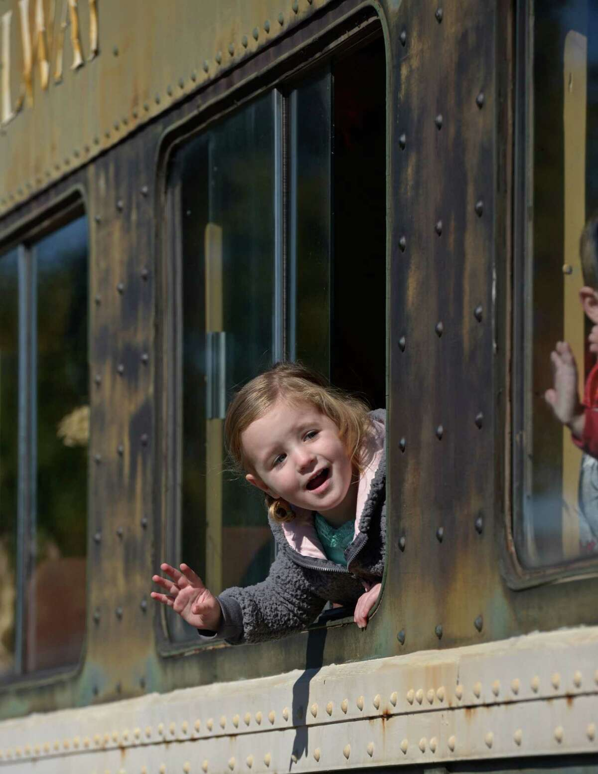 Ariana Jendry, 2, of Fairfield, waves to other riders boarding the Danbury Railway Museum's annual train to the pumpkin patch.