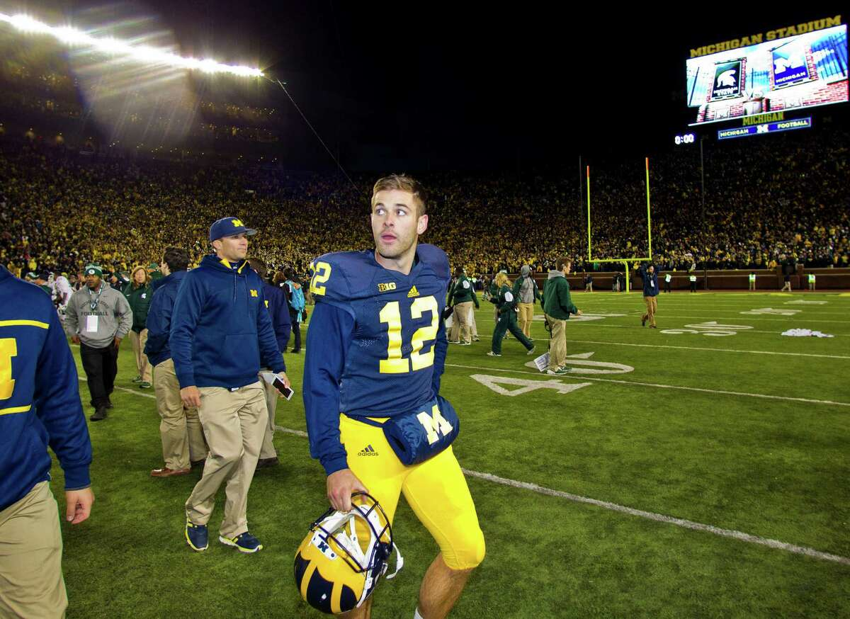 Michigan punter Blake O'Neill (12) walks off the field after an NCAA college football game against Michigan State in Ann Arbor, Mich., Saturday, Oct. 17, 2015. Michigan State's Jalen Watts-Jackson grabbed a flubbed punt by O'Neill and lumbered 38 yards into the end zone for a touchdown on the final play of the game, giving No. 7 Michigan State a shocking 27-23 win over No. 12 Michigan. (AP Photo/Tony Ding)