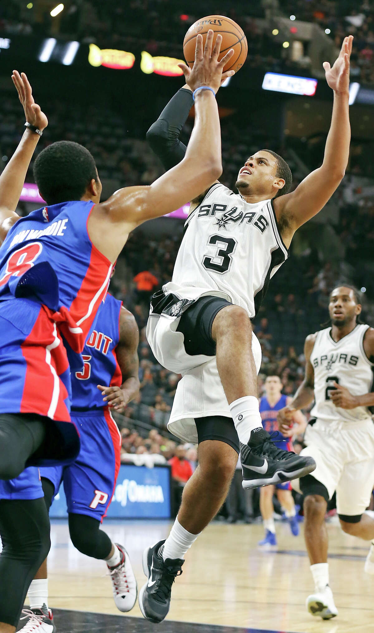 Spurs' Ray McCallum shoots around Pistons' Spencer Dinwiddie during first half action Sunday Oct. 18, 2015 at the AT&T Center.
