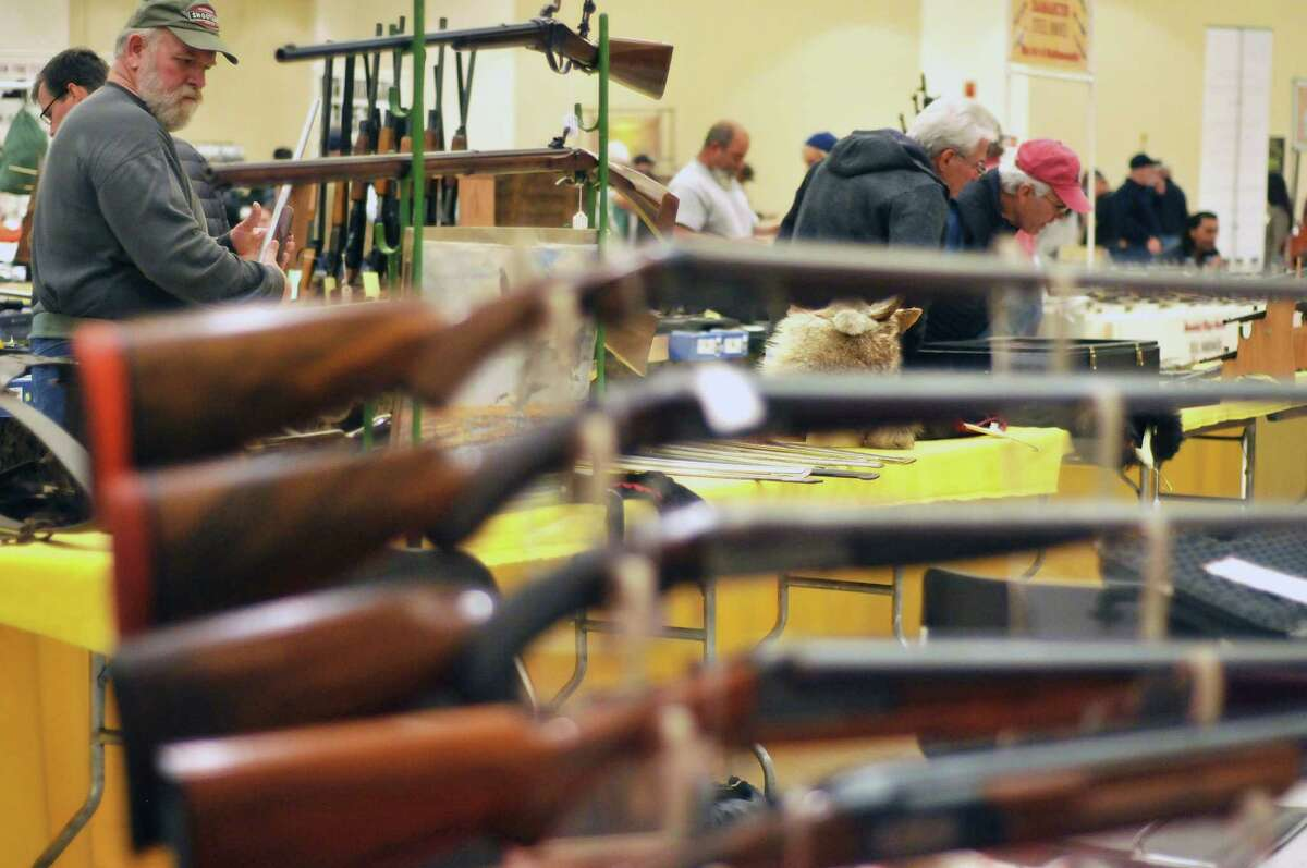 Visitors look over the different firearms for sale at the Arms Fair at the Saratoga Springs City Center on Sunday, Oct. 18, 2015, in Saratoga Spings, N.Y. This is the 31st year of the gun show, which featured 80 vendors with items spread out over 240 tables. The next large gun show in the area will be on January 23rd and 24th at the Empire State Plaza Convention Center. (Paul Buckowski / Times Union)