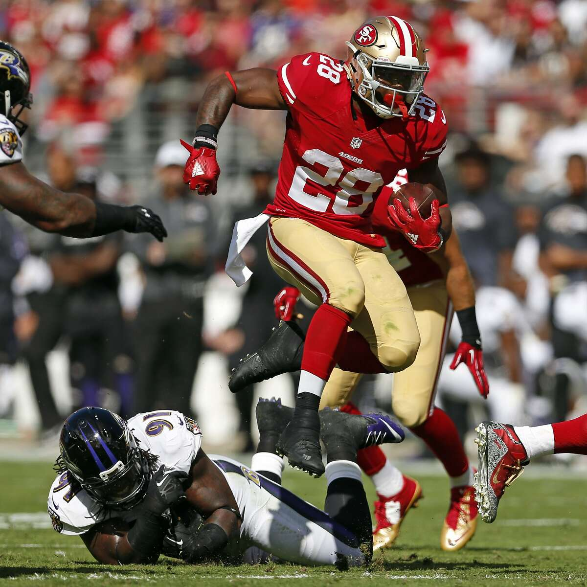 San Francisco 49ers' Carlos Hyde leaps over Baltimore Ravens' Courtney Upshaw in 1st quarter Niners' 25-20 win during NFL game at Levi's Stadium in Santa Clara, Calif., on Sunday, October 18, 2015.