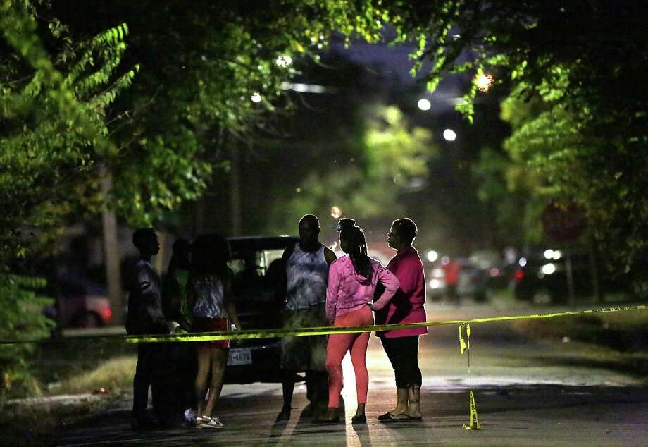 People gather in the street at the scene of a homicide in the 3100 block of Campbell Street, Sunday Oct. 18, in Houston. Photo: Jon Shapley, Houston Chronicle / © 2015 Houston Chronicle
