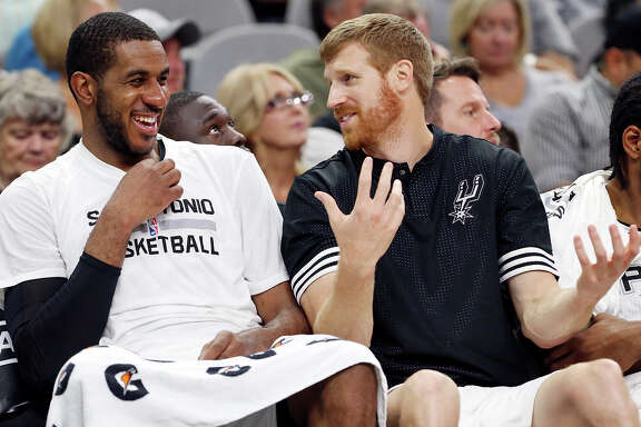 Spurs' LaMarcus Aldridge jokes with Matt Bonner while on the bench during second half action against the Detroit Pistons on Oct. 18, 2015 at the AT&T Center. The Spurs won the preseason game 96-92.