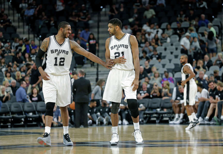 LaMarcus Aldridge jokes with Tim Duncan as the two stars return to the court as the Spurs  host the  Pistons  on October 18, 2015. Photo: Tom Reel / San Antonio Express-News