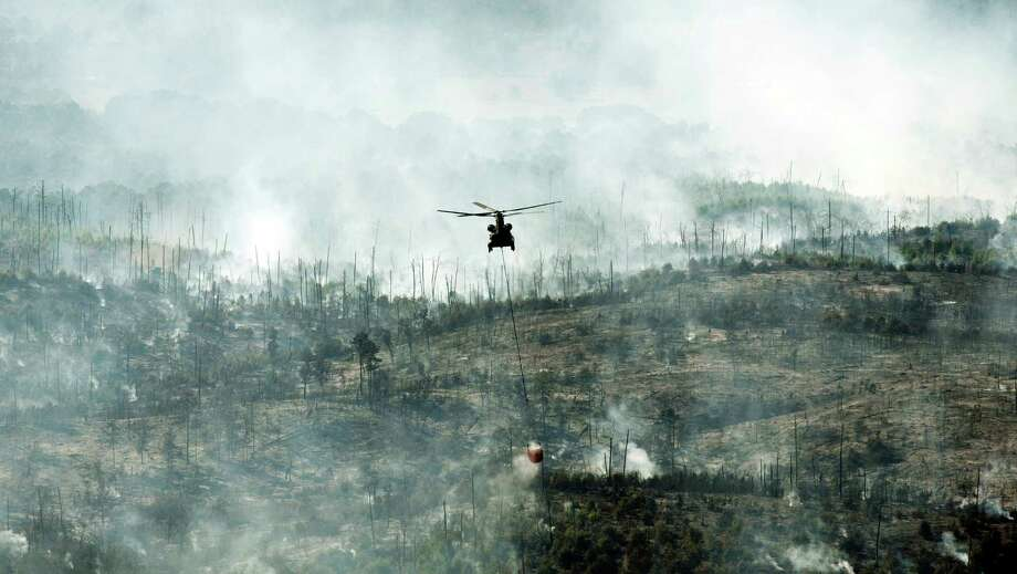 A helicopter on Friday drops water on the Hidden Pines fire in Smithville. A preliminary investigation indicates a farming accident sparked the wildfire.  Photo: Jay Janner, MBO / Austin American-Statesman