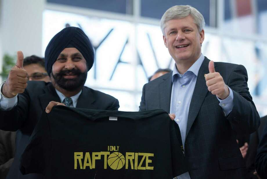 Conservative leader Stephen Harper poses with Nav Bhatia at a campaign rally in Mississauga, Ont. Sunday, Oct. 18, 2015.   Harper, one of the longest-serving Western leaders, is seeking a rare fourth term in Monday's election but polls show him narrowly trailing Liberal leader Justin Trudeau, the son of late Prime Minister Pierre Trudeau, one of Canada's most charismatic politicians.  (Jonathan Hayward/The Canadian Press via AP) Photo: Jonathan Hayward, SUB / The Canadian Press