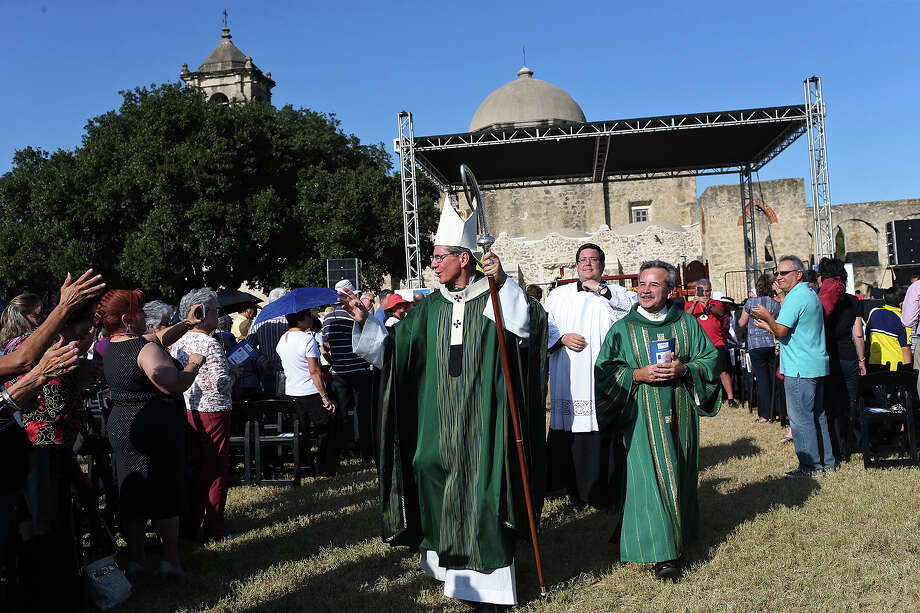 During the Recessional, San Antonio Archbishop Gustavo Garcia-Siller, center, waves to the crowd during a Mass celebrating the San Antonio Missions' World Heritage Inscription on the grounds of Mission San Jose, Sunday, Oct. 18, 2015. The service was part of a weekend-long celebration of the inscription. To the right of Garcia-Siller is Deacon Ray Jimenez. Photo: JERRY LARA, Staff / San Antonio Express-News / © 2015 San Antonio Express-News