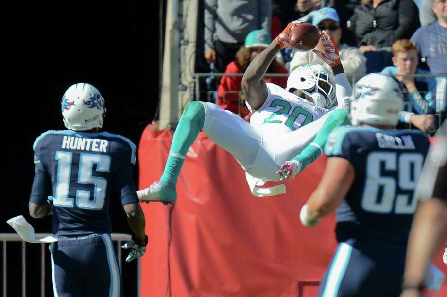 Dolphins safety Reshad Jones punctuates his interception return for a touchdown with a bit of acrobatics against the Titans. Photo: Mark Zaleski, FRE / FR170793 AP