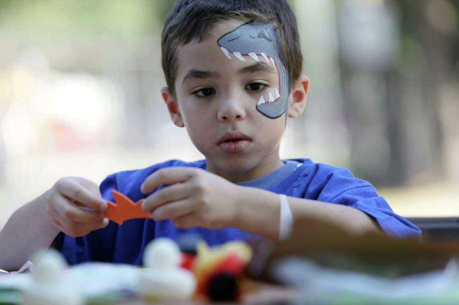 Dominic Chavez, 6, works on a Halloween mask as he and others took advantage of the pleasant weather Sunday to attend the Volunteer Houston 2015 Volunteer Fair at Sam Houston Park. Photo: Jon Shapley, Houston Chronicle / © 2015  Houston Chronicle
